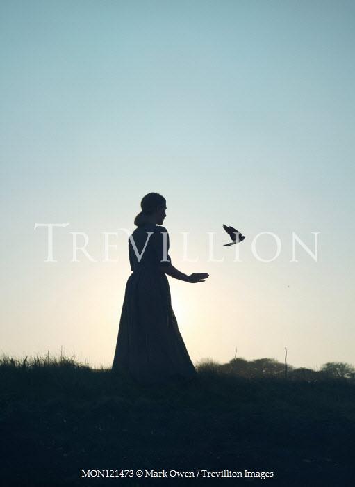 Mark Owen SILHOUETTED WOMAN WATCHING BIRD FLYING IN COUNTRYSIDE Women