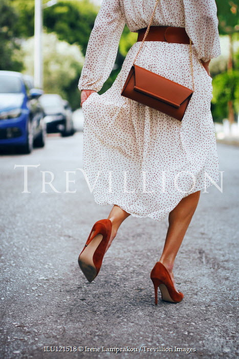 Irene Lamprakou Young woman in white dress and red high heels walking on road