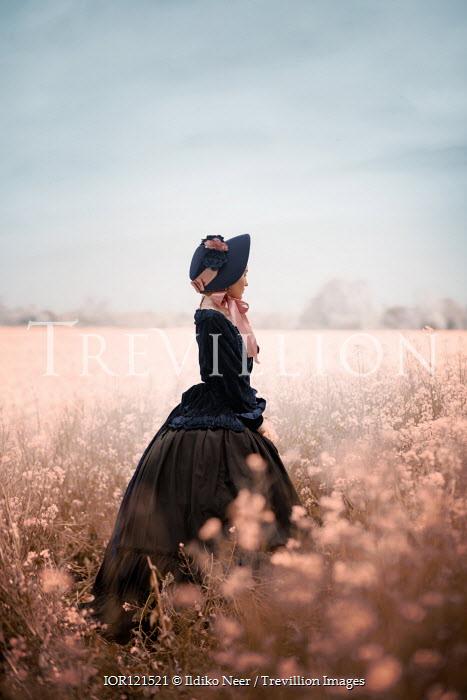 Ildiko Neer Victorian woman with hat in meadow