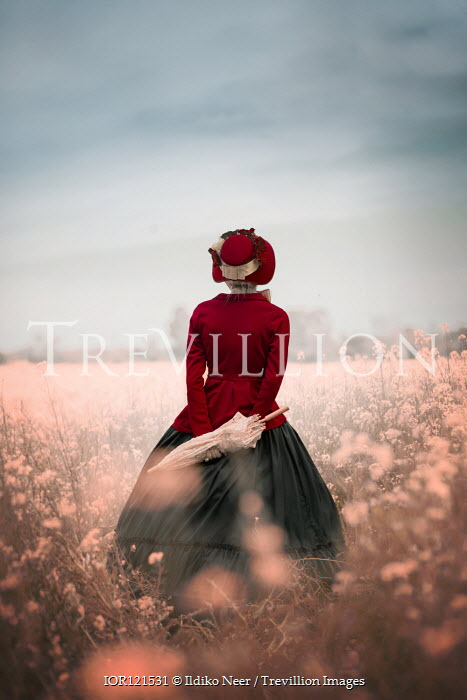 Ildiko Neer Victorian woman with hat in meadow