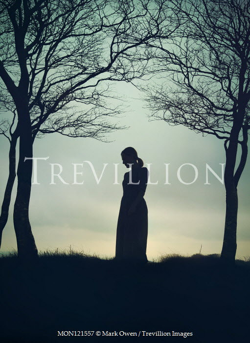 Mark Owen Silhouette of woman on hill under tree