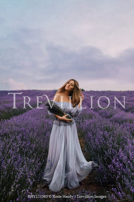 Rosie Hardy Young woman with blue dress standing in lavender field