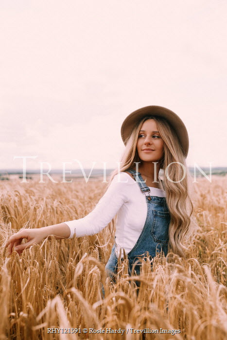 Rosie Hardy Young woman in denim overalls standing in wheat field