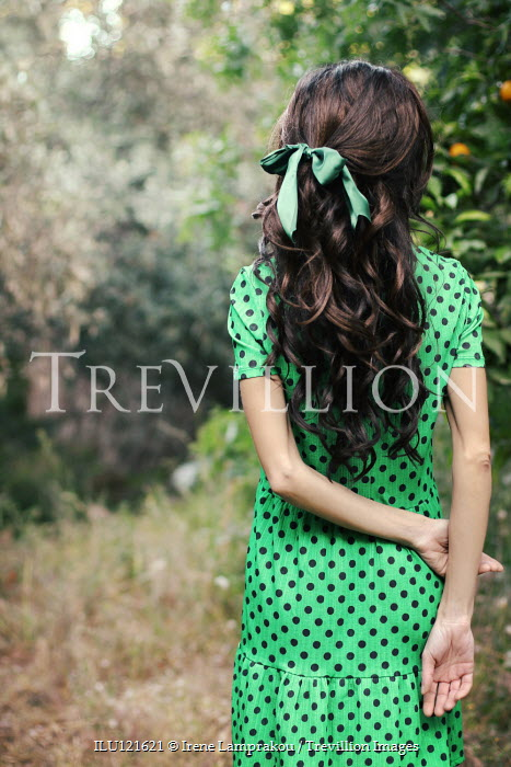 Irene Lamprakou Young woman in spotted green dress from behind