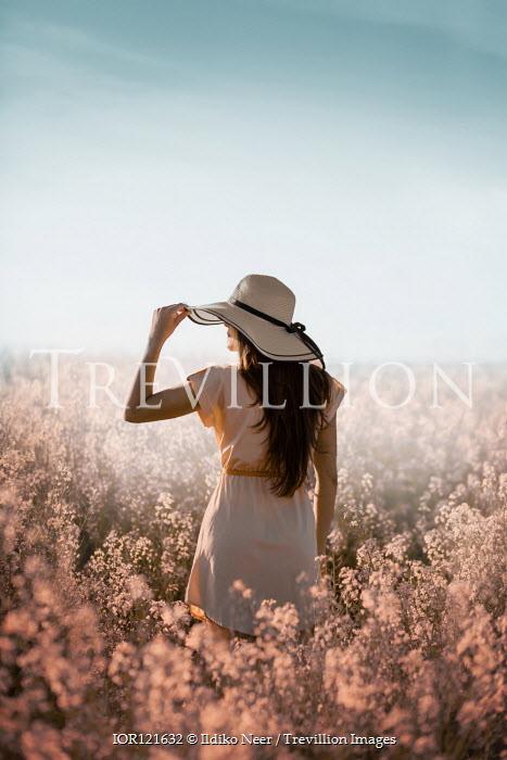 Ildiko Neer Woman in sun hat standing in meadow
