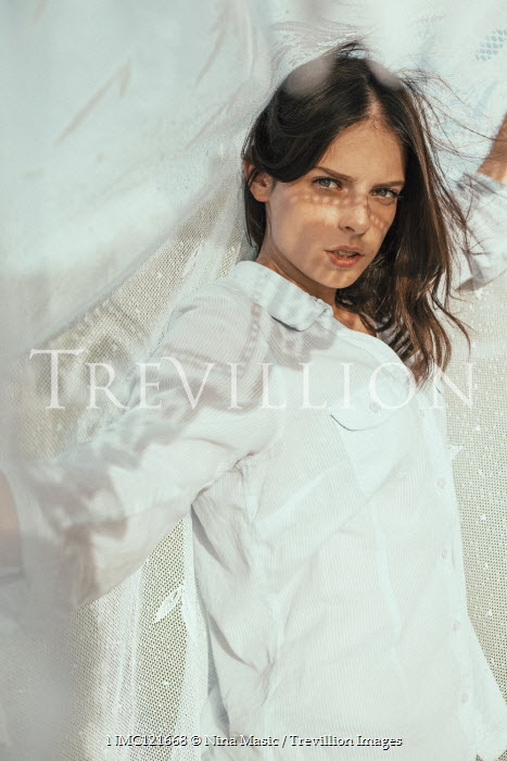 Nina Masic Young woman in white shirt under sheet