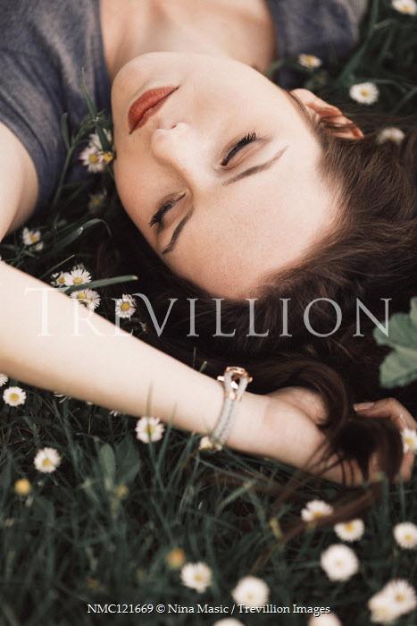 Nina Masic Young woman lying in grass