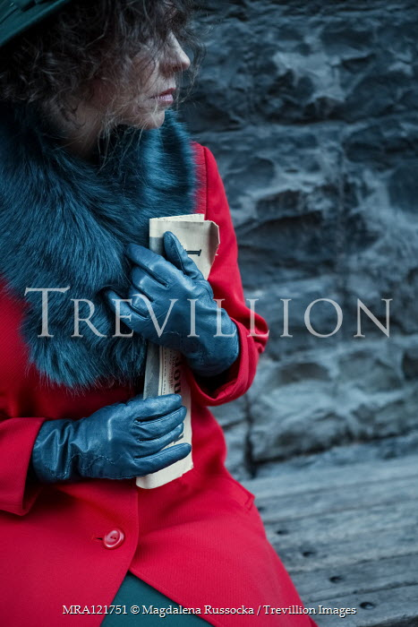 Magdalena Russocka close up of reto woman in red coat holding newspaper