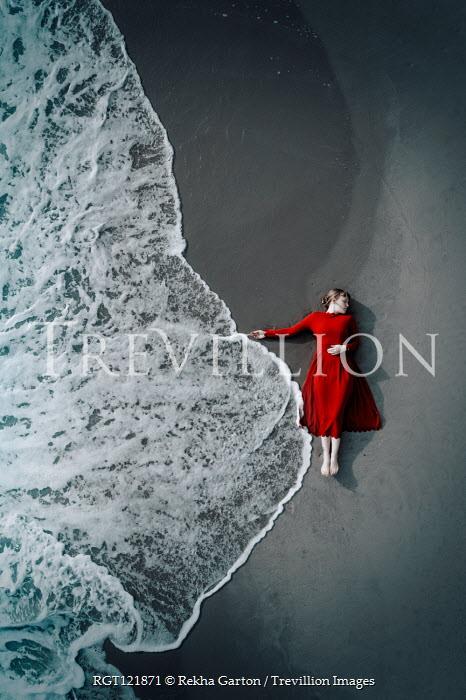 Rekha Garton WOMAN IN DRESS LYING ON BEACH WITH WAVE Women