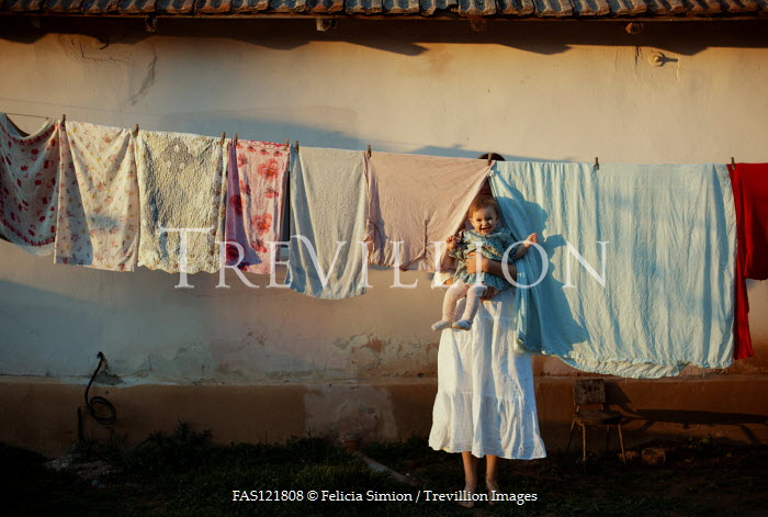 Felicia Simion WOMAN HOLDING BABY OUTDOORS BY WASHING LINE Children
