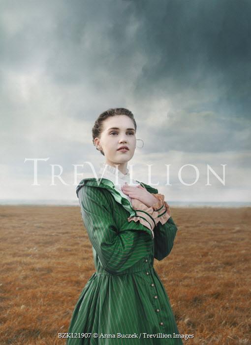 Anna Buczek GIRL IN GREEN DRESS STANDING IN STORMY COUNTRYSIDE Women
