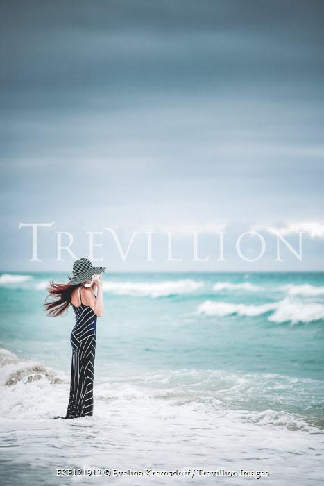 Evelina Kremsdorf WOMAN IN HAT WATCHING WAVES ON WINDY BEACH Women