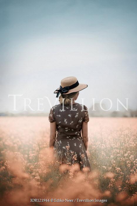 Ildiko Neer Blonde hair woman in straw hat standing in flower field