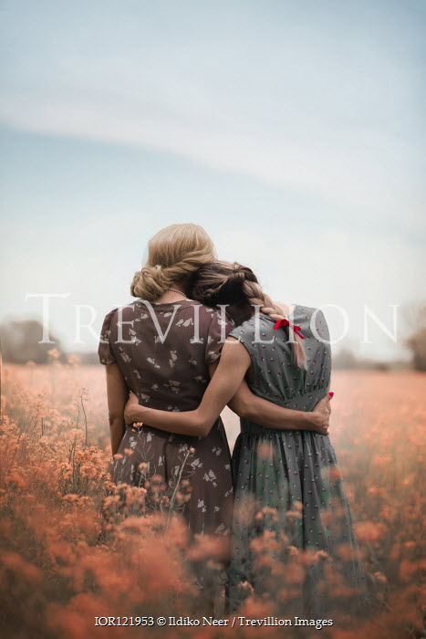 Ildiko Neer Two women hugging in summery field Women