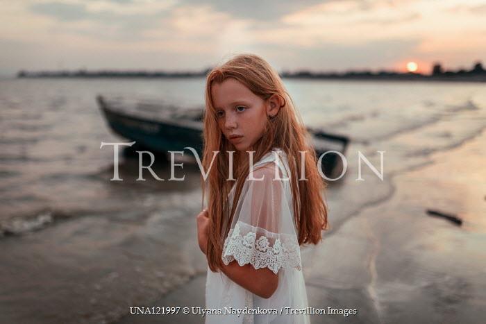 Ulyana Naydenkova LITTLE GIRL WITH RED HAIR STANDING ON BEACH AT SUNSET Children