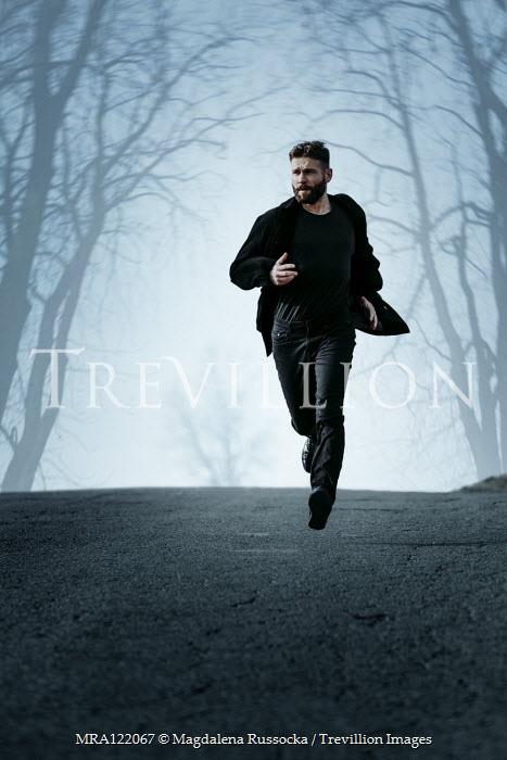 Magdalena Russocka modern man running on empty road in woods