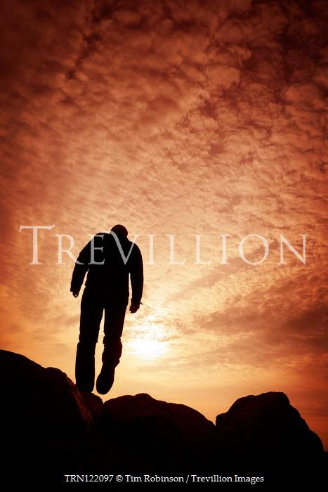 Tim Robinson MAN CLIMBING ROCKS AT SUNSET FROM BELOW Men