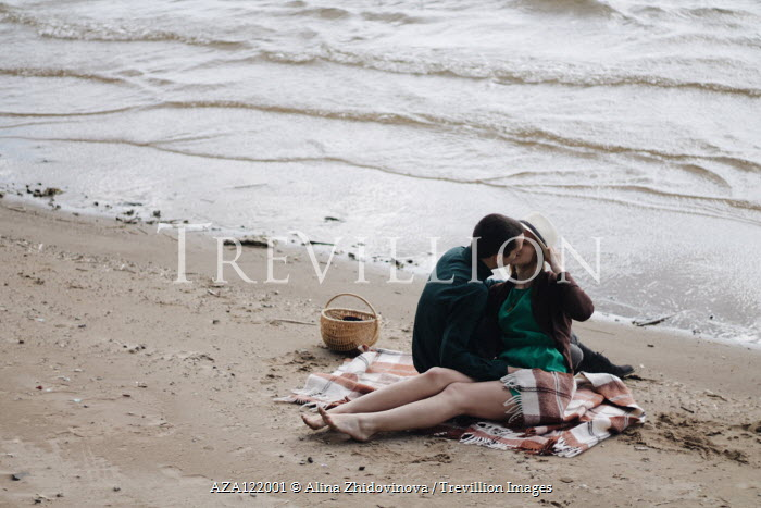 Alina Zhidovinova COUPLE SITTING AND KISSING ON RUG BY SEA Couples