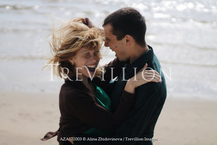 Alina Zhidovinova HAPPY COUPLE EMBRACING ON WINDY BEACH Couples