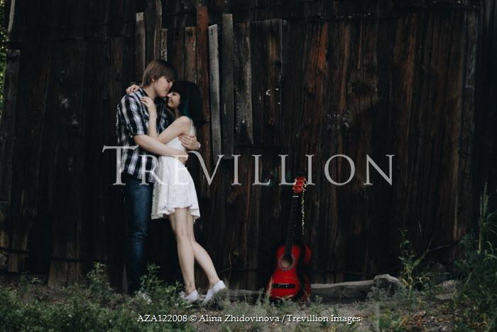 Alina Zhidovinova TEENAGE COUPLE EMBRACING BY FENCE WITH GUITAR Couples