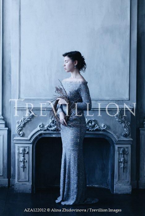 Alina Zhidovinova WOMAN IN LACY DRESS STANDING BY FIREPLACE WITH WREATH Women