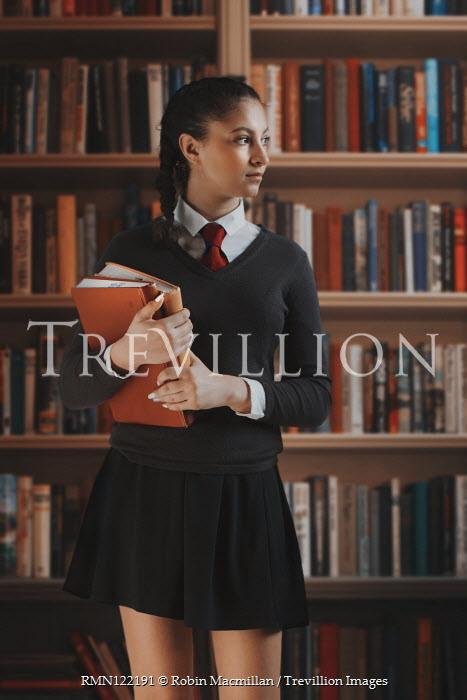 Robin Macmillan TEENAGE SCHOOLGIRL HOLDING BOOKS IN LIBRARY Children
