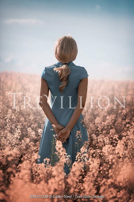Ildiko Neer Young woman in blue dress standing in meadow