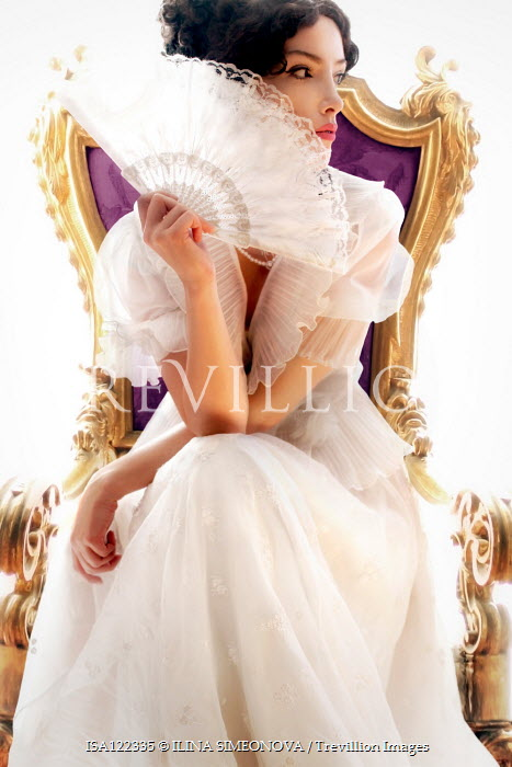 ILINA SIMEONOVA Young woman in white Victorian dress sitting by window