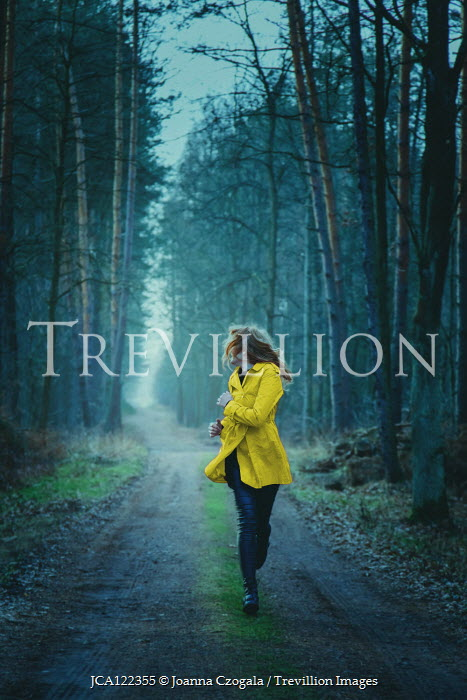 Joanna Czogala Scared woman in yellow coat running in forest