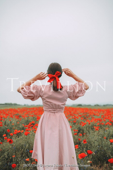 Jovana Rikalo Young woman in poppy field