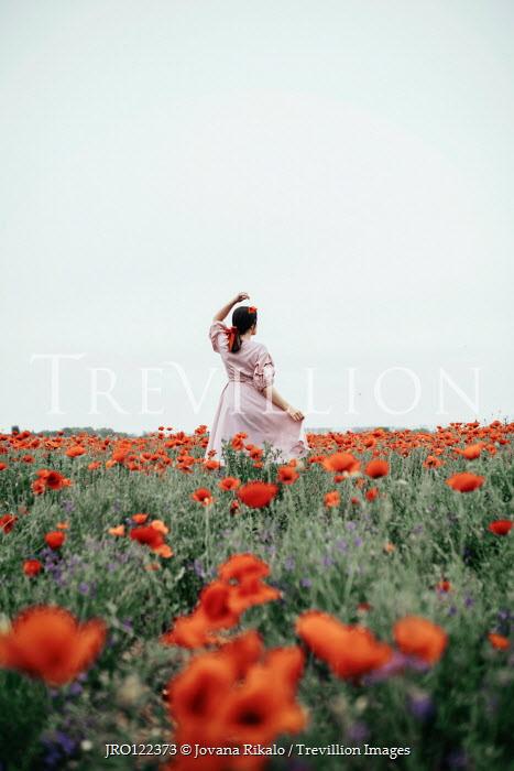 Jovana Rikalo Young woman in poppy field