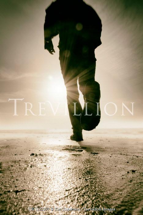Tim Robinson Man running on beach at sunset