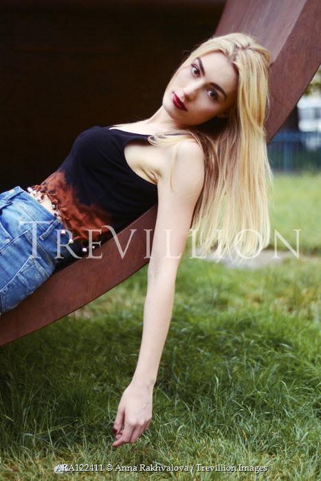 Anna Rakhvalova BLONDE GIRL IN SHORTS LYING IN SCULPTURE IN PARK Women