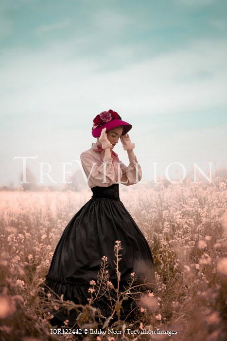 Ildiko Neer Victorian woman holding hat in flower field