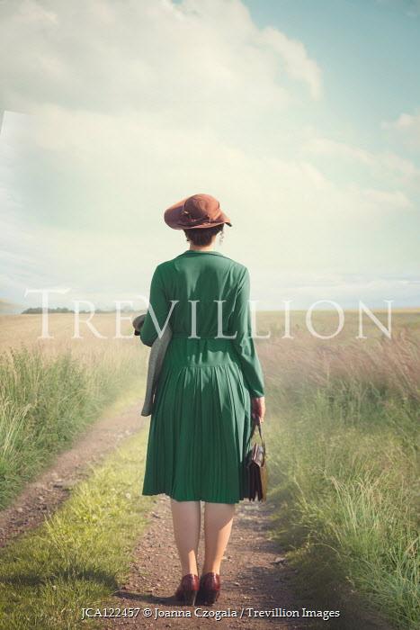 Joanna Czogala WOMAN IN HAT STANDING ON COUNTRY LANE IN SUMMER Women