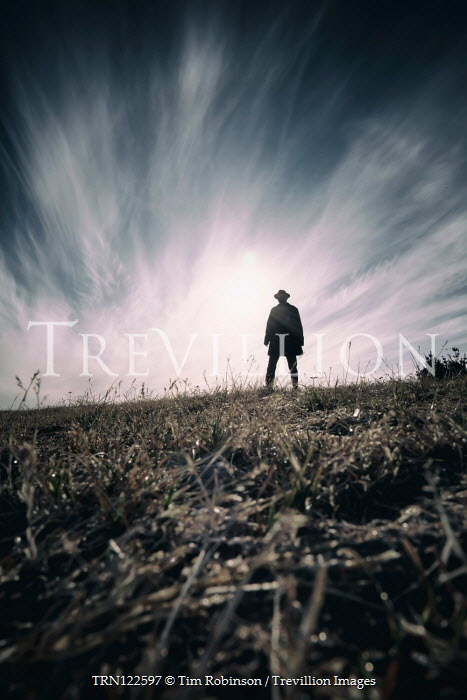 Tim Robinson SILHOUETTED MAN IN COAT AND HAT IN FIELD Men
