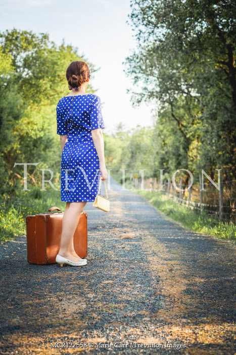 Marie Carr WOMAN IN BLUE DRESS WITH SUITCASE ON COUNTRY ROAD Women