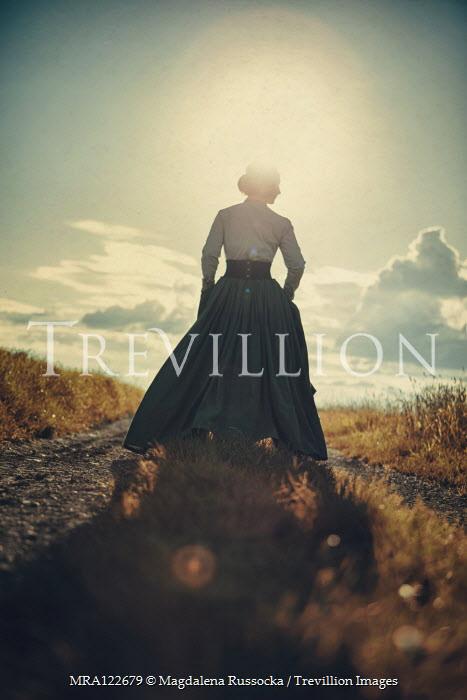 Magdalena Russocka historical woman walking on country road at sunset