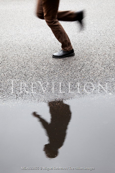 Miguel Sobreira RUNNING MAN REFLECTED IN PUDDLE IN ROAD Men