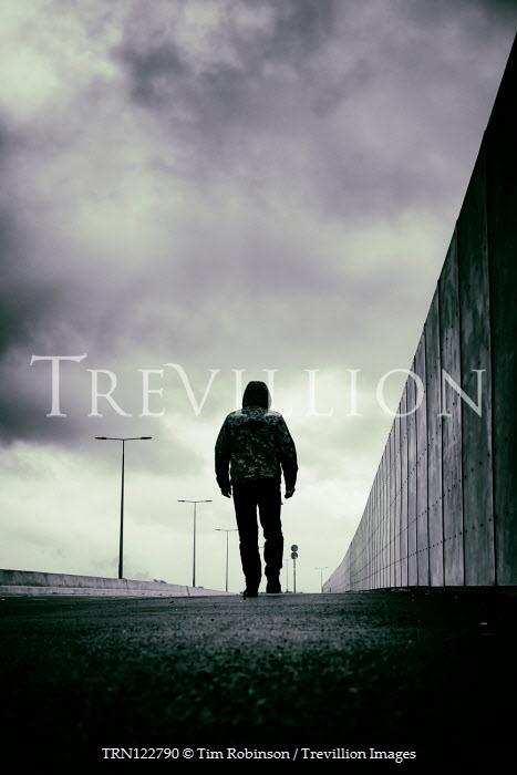 Tim Robinson Young man in hoodie walking on sidewalk