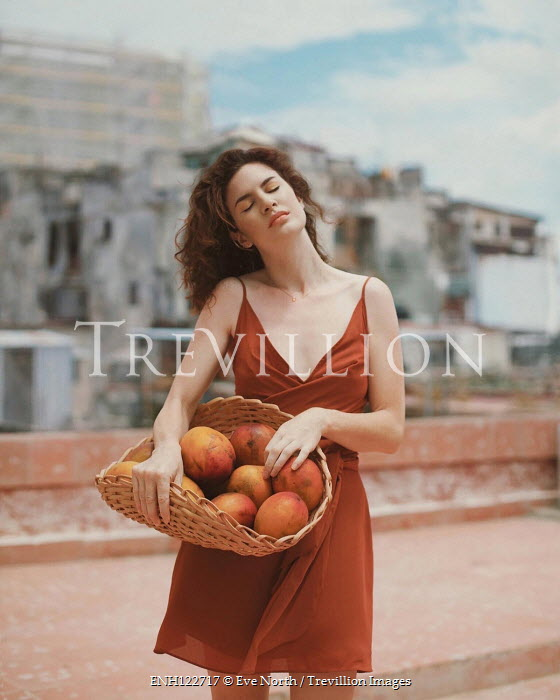 Eve North Young woman holding basket of mangoes