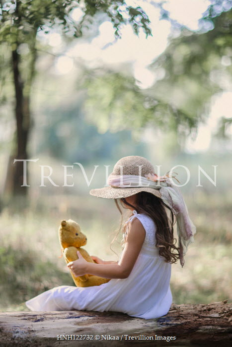 Nikaa Girl in straw hat with teddy bear in forest