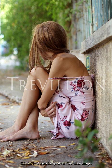 Irene Lamprakou Young woman in floral dress sitting on sidewalk