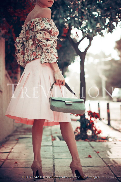 Irene Lamprakou Young woman in floral blouse and pink skirt on sidewalk