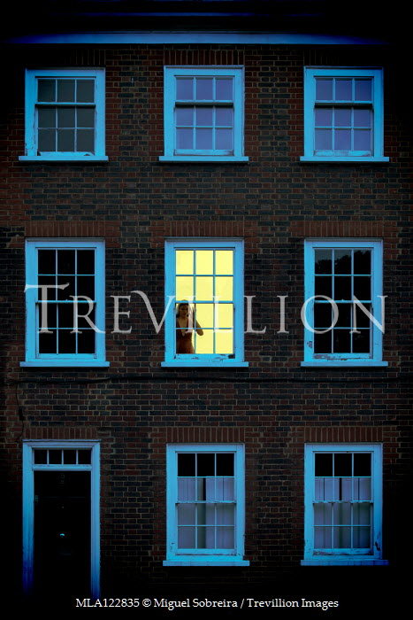 Miguel Sobreira Anxious woman at lit window of Victorian terrace house