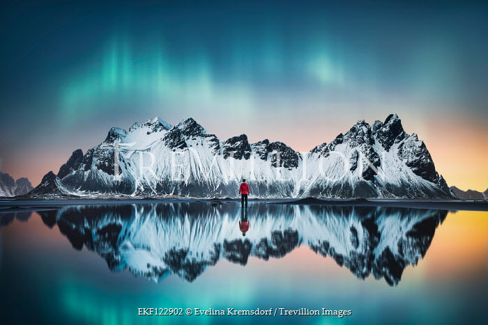 Evelina Kremsdorf MAN STANDING IN LAKE WITH SNOWY MOUNTAINS Men