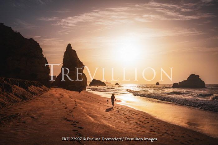 Evelina Kremsdorf WOMAN WITH DOG RUNNNG ON BEACH AT SUNSET Women