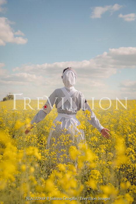 Joanna Czogala NURSE STANDING IN FIELD OF YELLOW FLOWERS Women