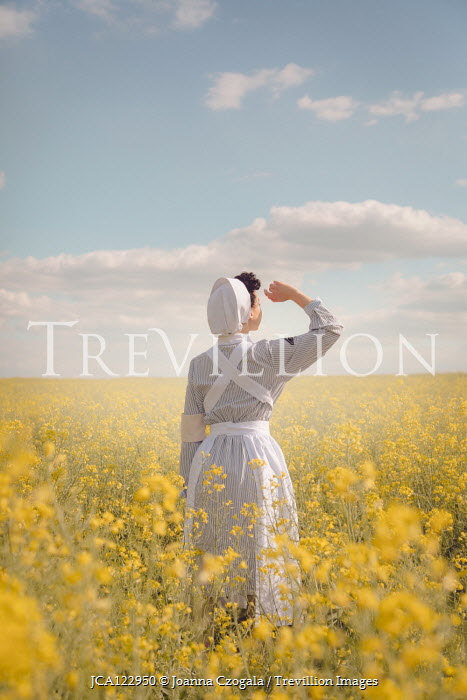 Joanna Czogala NURSE WATCHING SKY IN FIELD OF YELLOW FLOWERS Women