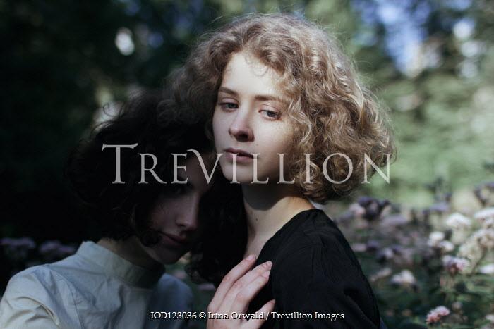 Irina Orwald TWO SERIOUS GIRLS HUGGING IN GARDEN Women